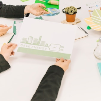 Крупный план руки человека с бумагой, показывающей концепцию энергосбережения