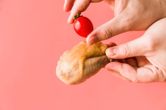 Close-up of a person's hands holding roasted chicken and red cherry tomatoes over pink background