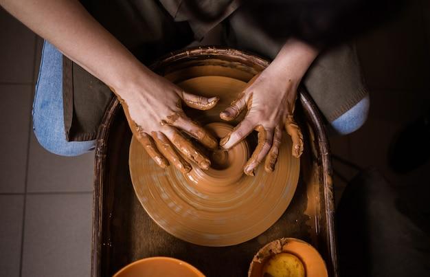 Крупный план рук человека, делающего миску из глины на ткацком станке в комнате