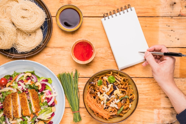 木製のテーブルでタイ料理の近くにペンでメモ帳に書いている人のクローズアップ