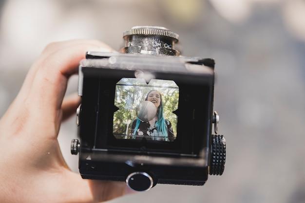 ヴィンテージカメラで女性の笑顔の写真を表示する人のクローズアップ