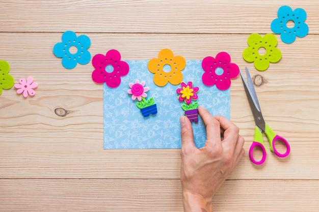 青いカードに花のパッチを貼っている人のクローズアップ