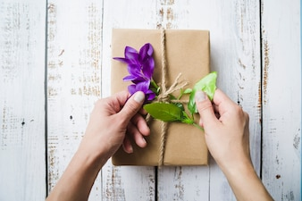 Close-up of a person touching the flowers on the packed parcel