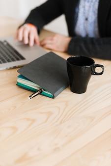 집에서 책상에 앉아 노트북에 일하는 사람의 클로즈업. 일기가 탁자 위에있다. 책상에서 일하십시오.