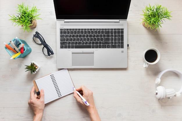 木製のオフィスの机の上の日記を書いている人のクローズアップ