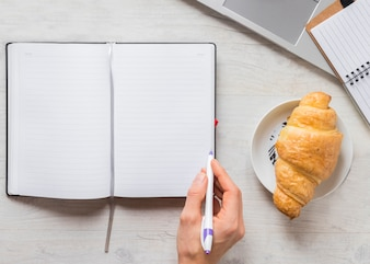 Close-up of a person writing in the diary with pen and croissant on plate over the wooden desk