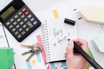 Close-up of a person writing to buy a house on spiral notepad with keys; calculator and house model