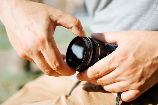 晴れた日の屋外で、カメラのレンズにプロの保護フィルターを置いている写真家の男性の手のクローズアップ。画像強調用の偏光、ソフトまたはndフィルター。
