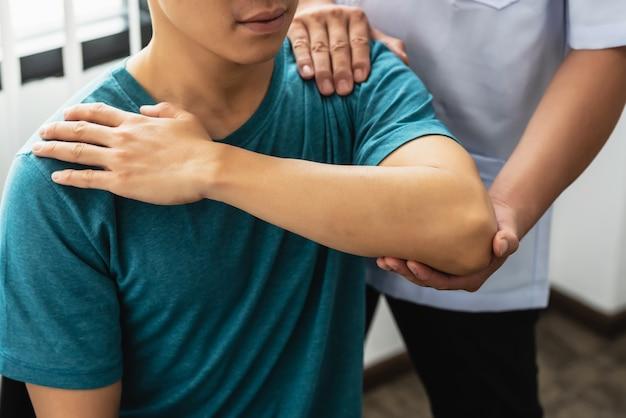 병원에서 남자 환자에게 스트레칭을 하는 물리치료사의 클로즈업.