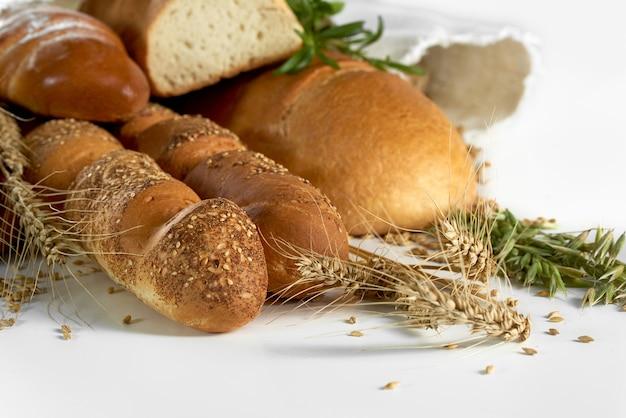 흰색 식품 영양 빵집 반죽에 격리된 채소와 밀을 곁들인 신선한 맛있는 빵 더미를 닫습니다. 유기농 건강 개념을 먹는 제빵 제빵입니다.