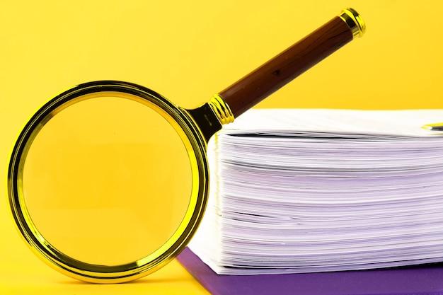 黄色の背景に、検証を待っている未完成のドキュメントの山、虫眼鏡のクローズアップ。ビジネスと教育の概念。コピースペース