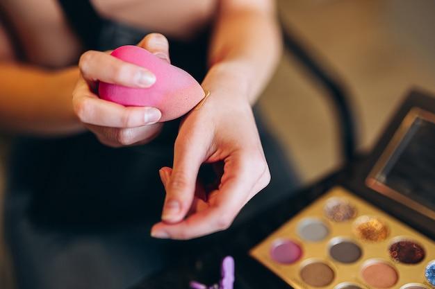 손에 핑크 뷰티 블렌더의 클로즈업입니다. 뷰티 블렌더는 컨실러를 선택합니다.