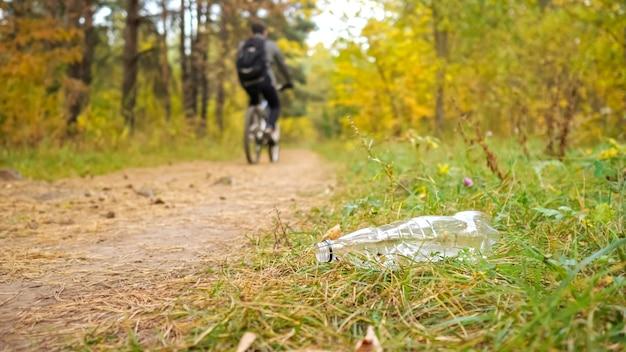 Закройте пластиковую бутылку в траве на фоне велосипедиста в лесу. выборочный фокус