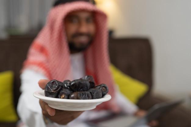 ターバンを身に着けているアラブのビジネスマンによってもたらされた日付のプレートのクローズアップ