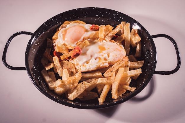 スクランブルエッグまたはチョリソとチップの選択的な焦点を持つ卵のプレートのクローズアップ