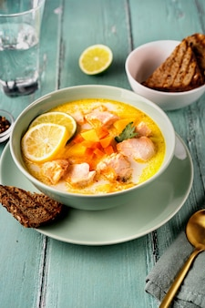 Закройте тарелку с вкусным рыбным супом из лосося