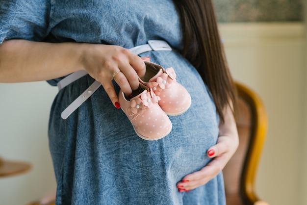 Крупный план беременной женщины, держащей на животе розовые детские пинетки в джинсовом платье