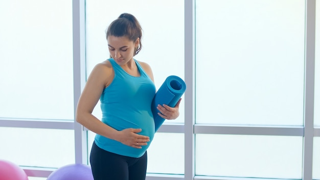 スポーツマットと妊娠中の女性の腹のクローズアップ。