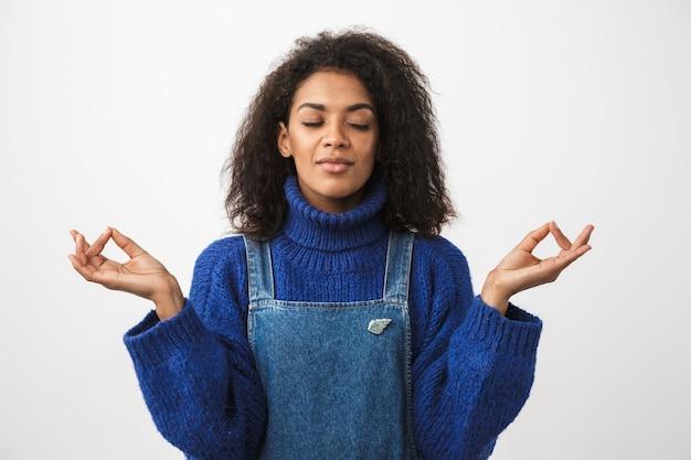 白の上に孤立して立っているセーターを着て、瞑想しているかなりアフリカの女性のクローズアップ