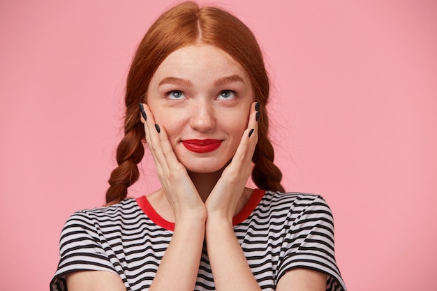 2つの三つ編みのとても素敵な心温まる赤毛の女の子のクローズアップは彼女の顔の近くに手を保ち、上向きのインスピレーションで夢のように見て、愛について考え、孤立しています