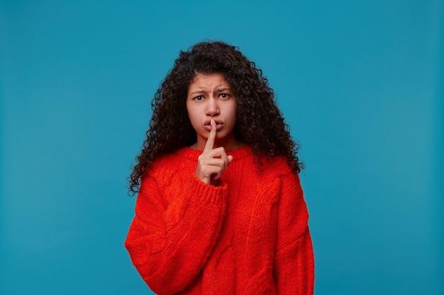 Крупным планом довольно напуганная женщина в красном свитере, стоящая на синей стене
