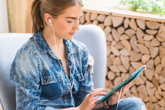 Close-up of a pretty woman listening and using digital tab