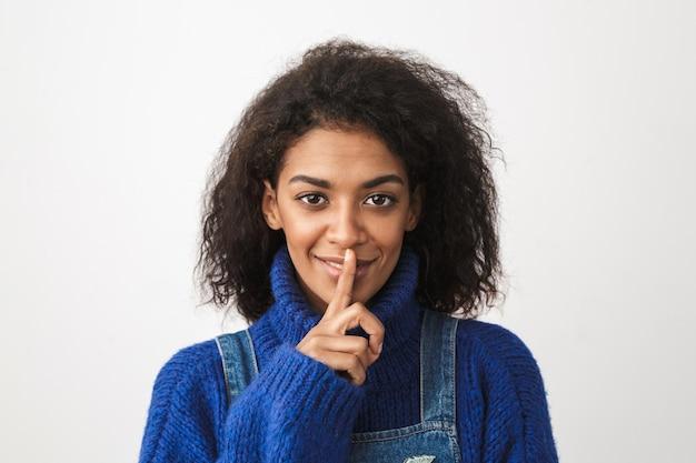 고립 된 서 스웨터를 입고 꽤 젊은 아프리카 여자의 닫습니다, 침묵 제스처를 보여주는