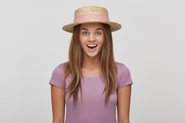 ピンクのリボンと麦わら帽子のかなり若い女性のクローズアップは喜んで喜んで喜んで見える