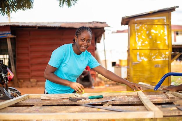 그녀가 작업하고 싶은 나무를 측정하는 전문 목수의 클로즈업