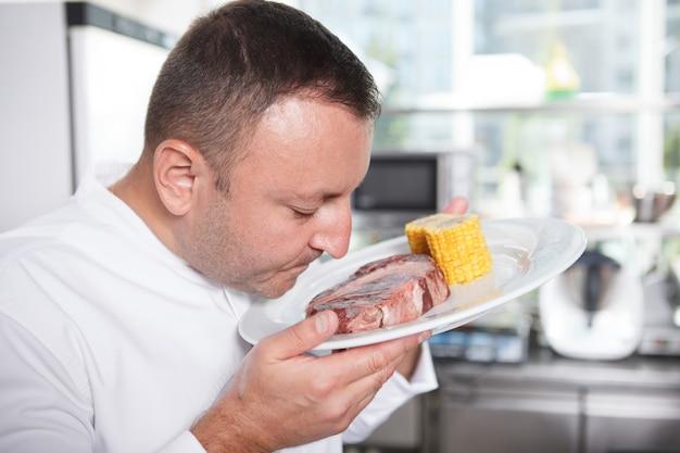Крупным планом профессиональный шеф-повар нюхает стейк из говядины перед его приготовлением