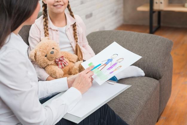 Крупный план профессионального психолога, глядя на семейный рисунок, нарисованный девочкой с ребёнком