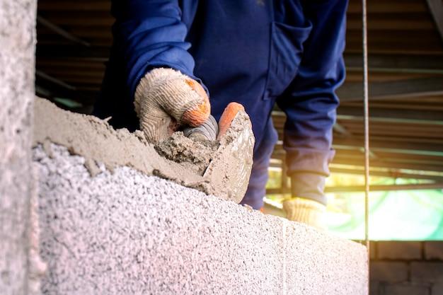 Крупный план профессионального рабочего, использующего кухонный нож для строительства кирпичной стены из цементных кирпичей и цемента. бизнес-идеи и строительная индустрия