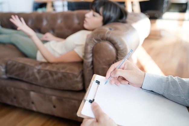 Крупный план психолога, делающего записи в буфере обмена, в то время как его пациентка лежит на кушетке и рассказывает о своих проблемах