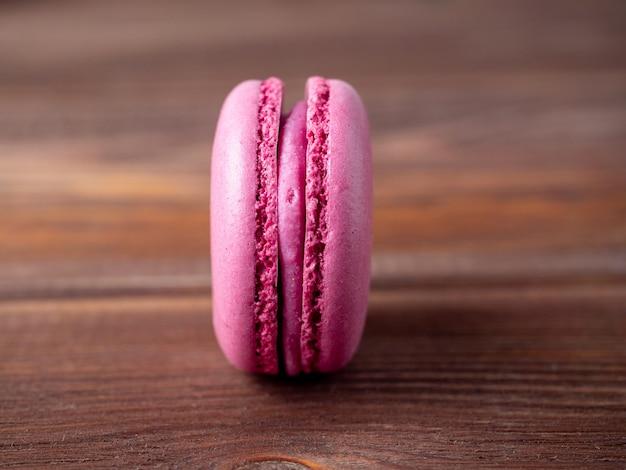 Крупный план пурпурного миндального печенья на коричневом деревянном фоне. вкусный сладкий французский десерт.