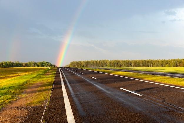빗 속에서 무지개의 클로즈업입니다. 무지개 색깔은 젖은 고속도로에 직접 떨어집니다.