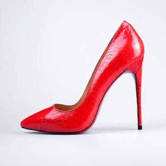 Крупным планом красные высокие каблуки на белом фоне