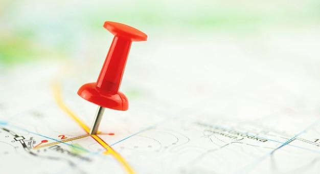 Крупный план красной канцелярской кнопки на карте города, фото композиции выборочного фокуса