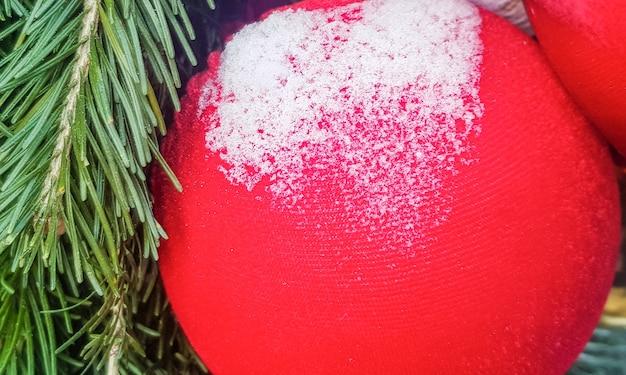 눈으로 덮인 빨간색 빛나는 크리스마스 공의 클로즈업, 축제 장식 및 배경의 개념.