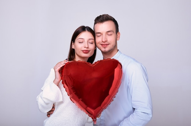 白い背景の上の赤いハート型の風船と恋にロマンチックなカップルのクローズアップ
