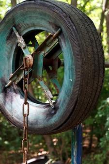 도시 공원에서 두꺼운 나무 사이에서 오래 된 타이어에서 거친 집에서 만든 시뮬레이터의 근접
