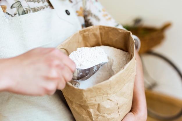 유기농 상점에서 쇼핑백에서 밀가루를 가져가는 판매원의 클로즈업.