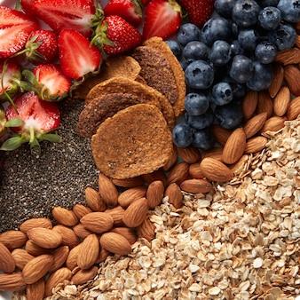 Крупный план набора ингредиентов, овсянки, мюсли, миндаля, закусок, черники и половинок клубники, вид сверху. здоровый витаминный завтрак