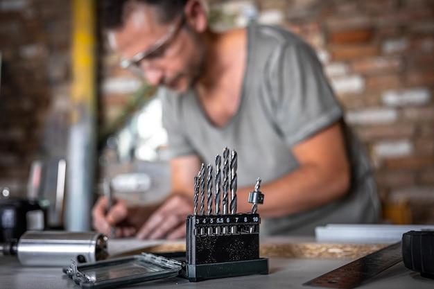 ワークショップのジョイナーの作業テーブル上の木製ドリルのセットのクローズアップ。