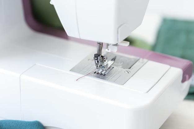Крупный план лапки швейной машины с фиолетовой нитью, готовой к работе и шитью нового дизайнерского изделия. концепция дизайнерского пошива.