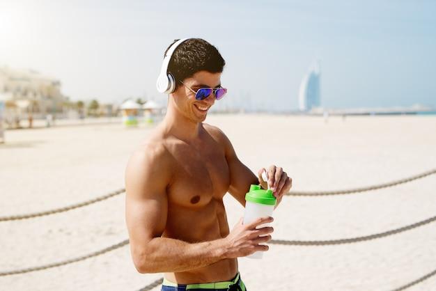Закройте без рубашки мускулистый мужчина фитнес на пляже, держа освежающий напиток, слушать музыку и подготовка к тренировке.