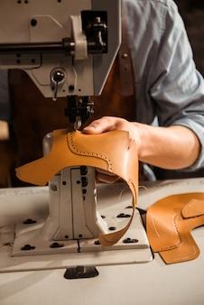 Крупным планом сапожника с помощью швейной машины