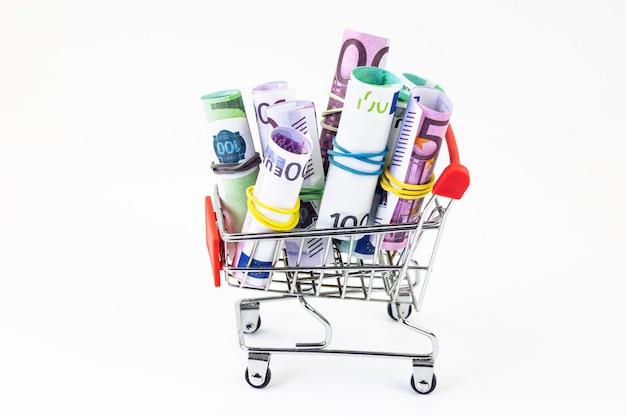 흰색 배경에 고립 된 유로 및 달러 지폐의 전체 쇼핑 카트의 근접. 대출, 투자, 연금, 저축, 금융, 담보, 부채, 모기지, 금융 위기의 개념.
