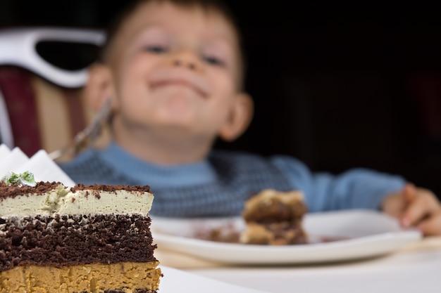 テーブルの上のデザート用の焼きたてのレイヤーケーキのスライスのクローズアップとその後ろに歓喜でニヤリと笑う遊び心のある小さな男の子