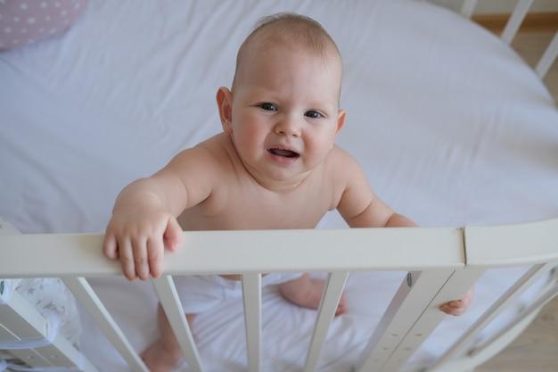 ベビーベッドに立っている小さな子供のクローズアップ。幼児はベッドで寝たくない。