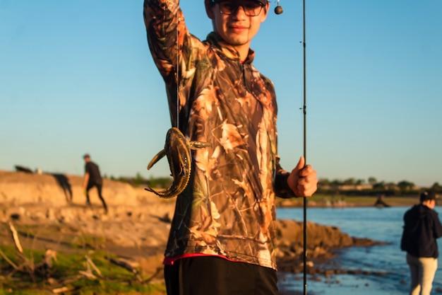 Крупным планом - маленькая рыбка, зацепившаяся за удочку молодого человека.